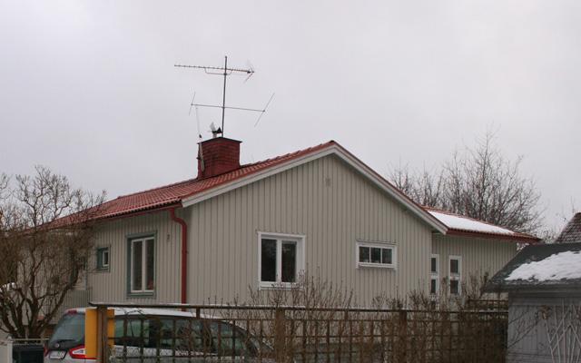Vitt, enplanshus med vinkel och sadeltak, före taklyftet.