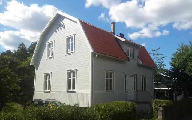 Vitt, tvåplanshus med förhöjt väggliv, efter taklyftet med ny takvåning.
