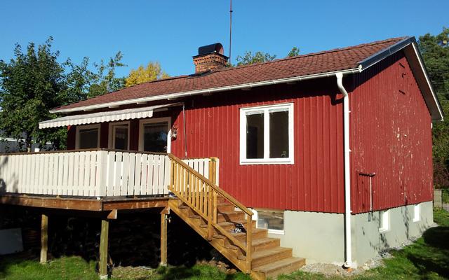 Rött, enplanshus med mansardtak och förhöjt väggliv, före taklyftet.