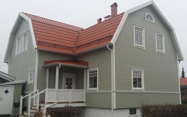 Grönt, tvåplanshus efter taklyftet med ny takvåning.