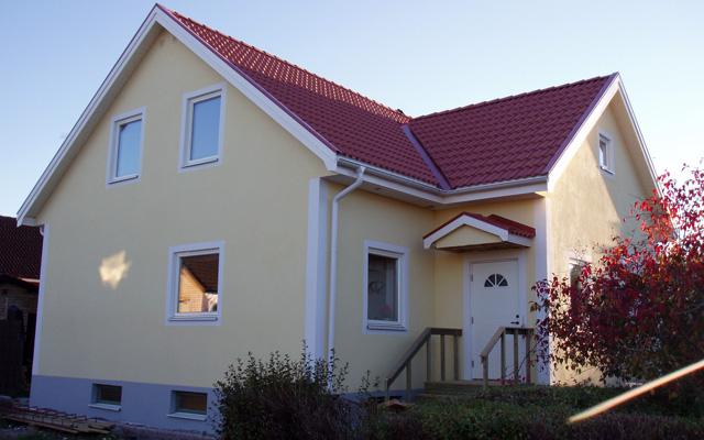 Tvåplanshus med sadeltak, efter taklyftet med ny takvåning och utbyggnad av vinkel.