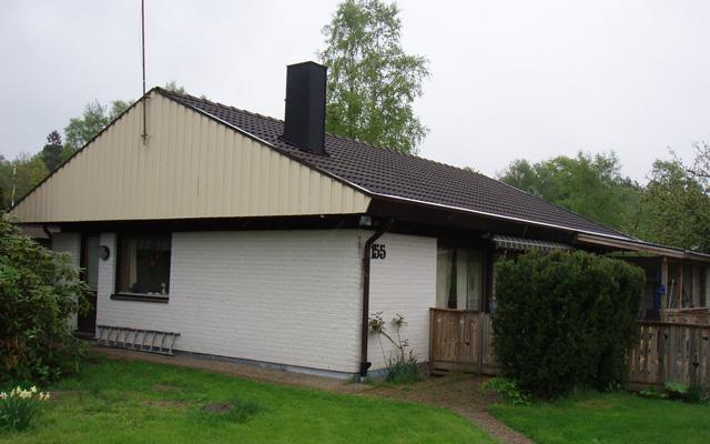 Vitt, enplanshus med sadeltak och kupa, före taklyftet.