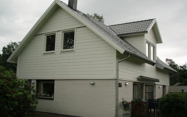 Vitt, tvåplanshus med sadeltak och kupa, efter taklyftet med ny takvåning.