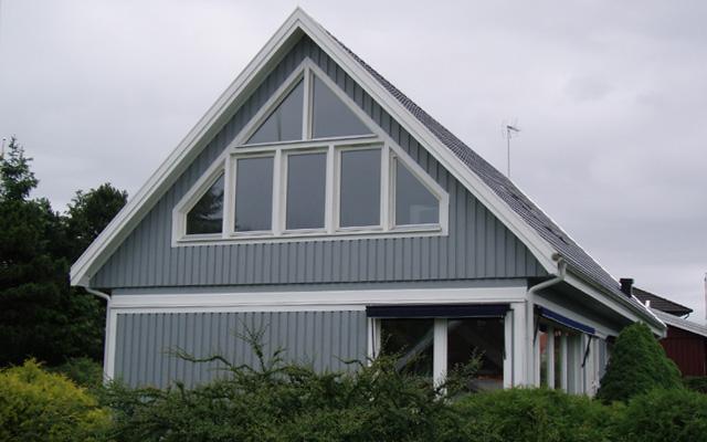 Vitt, tvåplanshus med sadeltak och fasadfönster, efter taklyftet med ny takvåning.