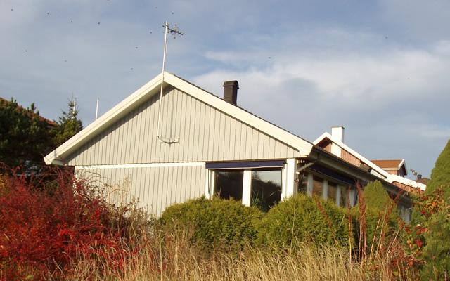 Vitt, enplanshus med sadeltak och fasadfönster, före taklyftet.