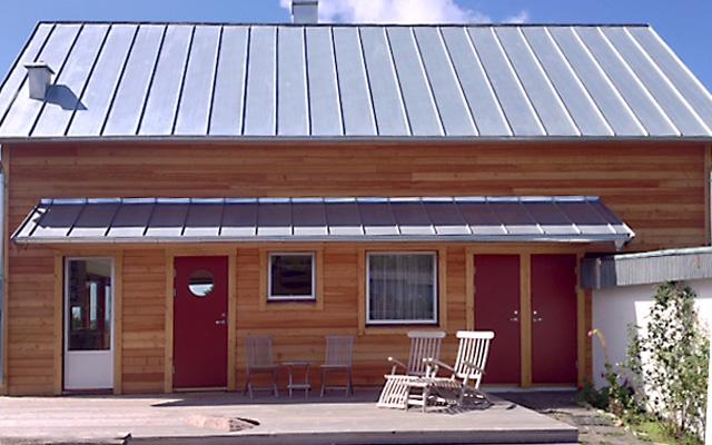 Tvåplanshus i trä med sadeltak i plåt, efter taklyftet med ny takvåning.