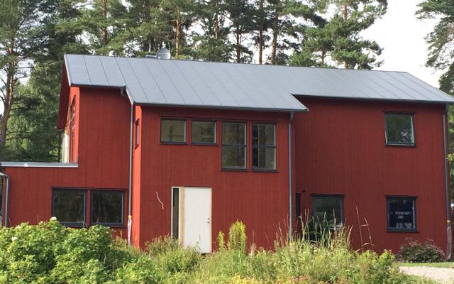 Rött, tvåplanshus med sadeltak och flera utbyggnader, efter taklyftet med ny takvåning.
