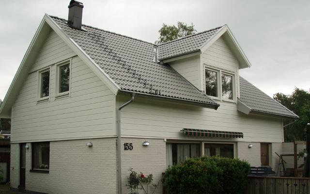 Vitt, tvåplanshus med sadeltak och mindre kupa, efter taklyftet med ny takvåning.