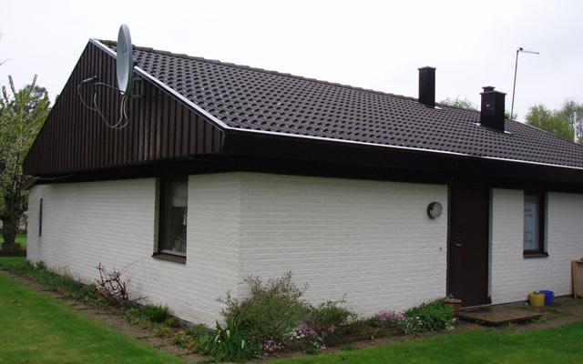 Vitt, tegelhus med sadeltak och mindre kupa, före taklyftet.