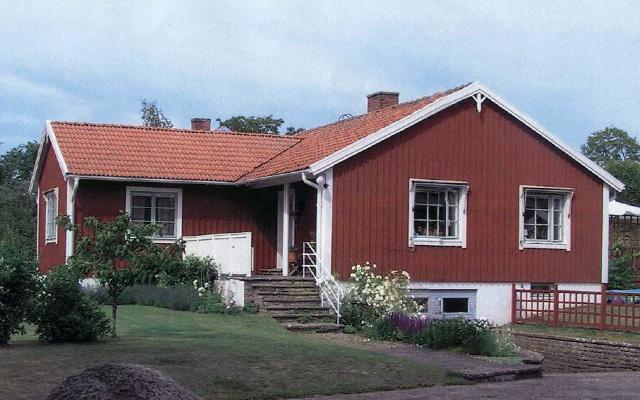 Rött, enplanshus med sadeltak i vinkel, före taklyftet.