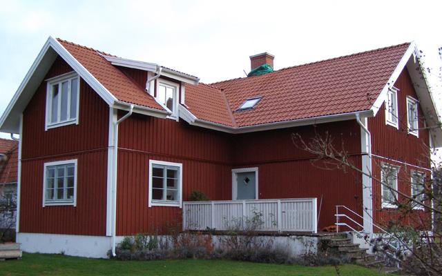 Röd, fullvåning med sadeltak i vinkel, efter taklyftet med ny takvåning.